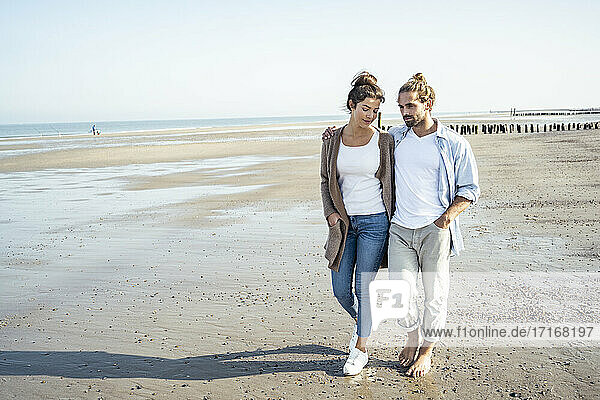 Young couple with hands in pockets taking walk on beach during sunny day