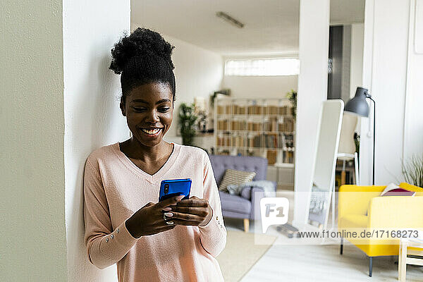 Smiling woman shopping over mobile phone while standing at home