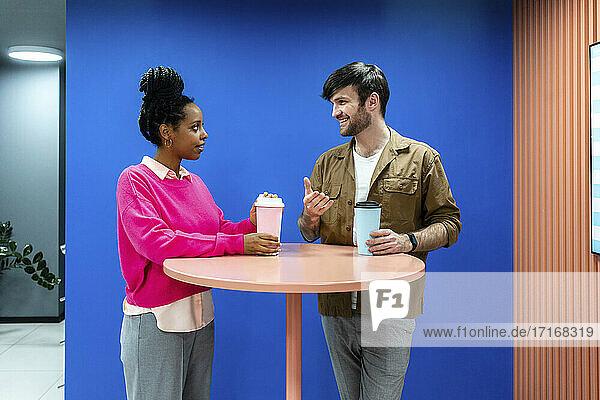 Kreativer männlicher und weiblicher Kollege mit wiederverwendbarem Kaffeebecher im Gespräch in der Cafeteria am Arbeitsplatz Kreativer männlicher und weiblicher Kollege mit wiederverwendbarem Kaffeebecher im Gespräch in der Cafeteria am Arbeitsplatz