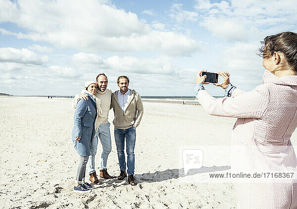 Group of friends taking smart phone photos at beach