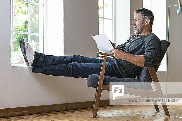 Mature businessman looking away while sitting with paper on armchair at home
