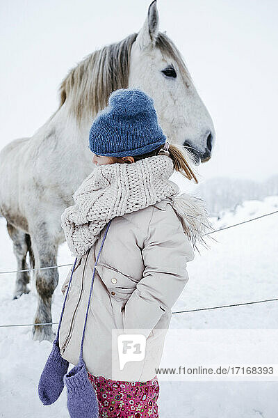 Girl looking away while standing in front of horse