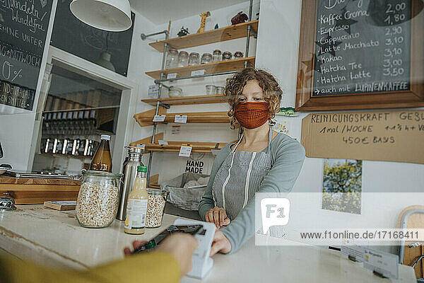 Mature customer paying through smart phone in zero waste store during COVID-19