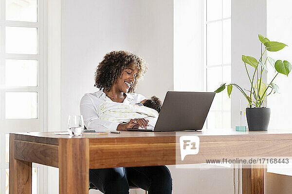 Smiling woman holding baby while working on laptop sitting at home office