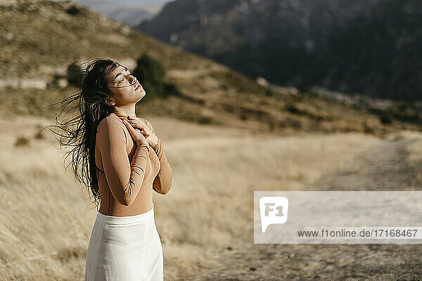 Young woman with eyes closed standing in field during sunset