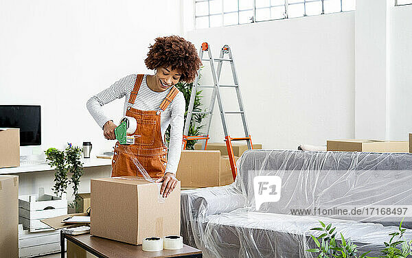 Afro woman packing box with adhesive tape while relocation in new home