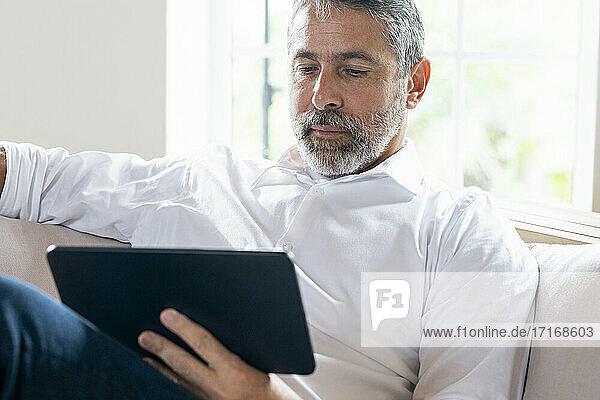Geschäftsmann  der ein digitales Tablet benutzt  während er zu Hause auf dem Sofa sitzt Geschäftsmann, der ein digitales Tablet benutzt, während er zu Hause auf dem Sofa sitzt