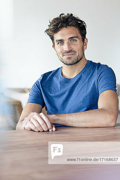 Mid adult man smiling while sitting by table at home