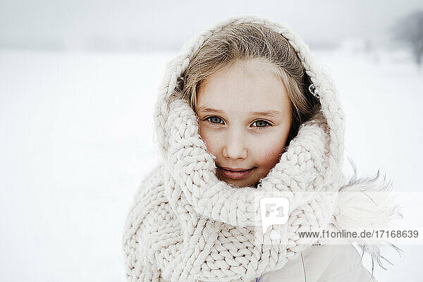 Small girl covered with knitted scarf during winter