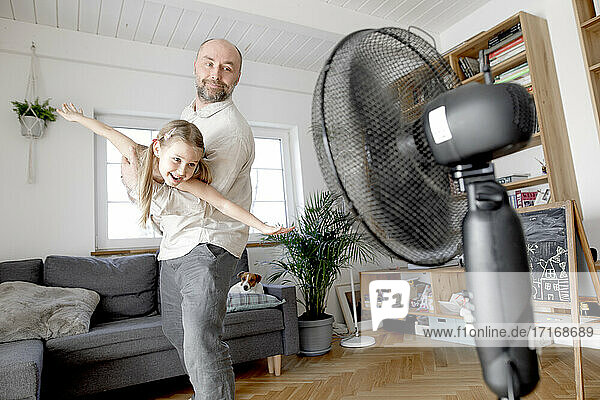 Father playing with cheerful daughter in front of electric fan at home