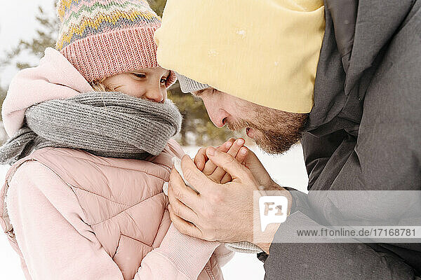 Close-up of father warming daughter's cold hands during winter