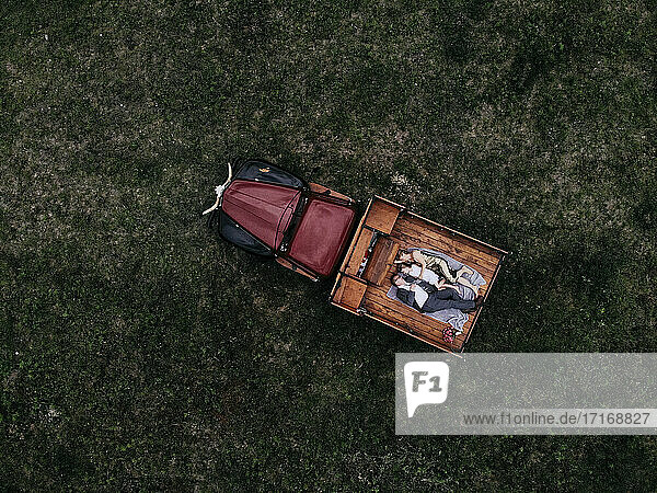 Aerial view of family lying on pick-up truck over grassy land