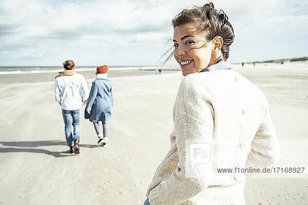 Porträt einer jungen Frau  die am Sandstrand spazieren geht  mit zwei Personen im Hintergrund Porträt einer jungen Frau, die am Sandstrand spazieren geht, mit zwei Personen im Hintergrund