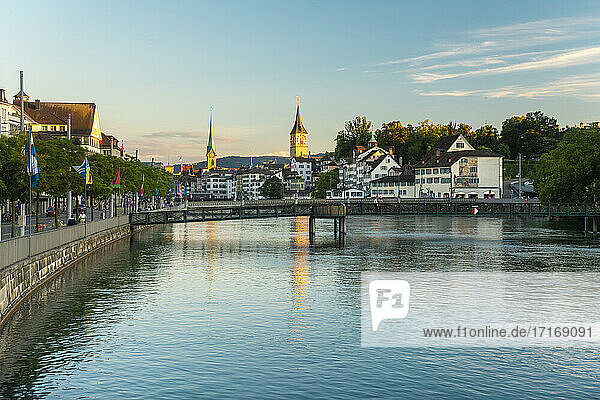 Limmat river waterfront with St. Peter's and Fraumunster Church in Zurich  Switzerland