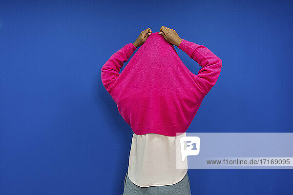 Female professional with arms raised removing sweatshirt in office
