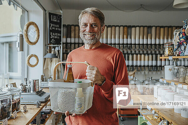 Smiling mature male customer holding basket of groceries in zero waste shop