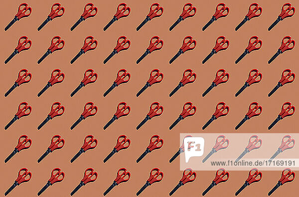 Pattern of rows of scissors against red background