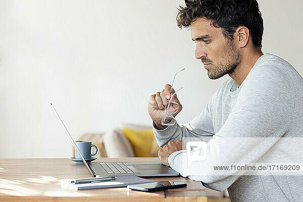 Man holding eyeglasses while working on laptop at home