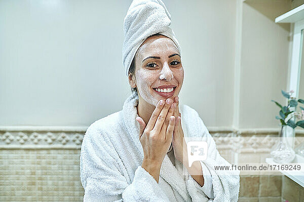 Smiling woman applying cream on face in bathroom