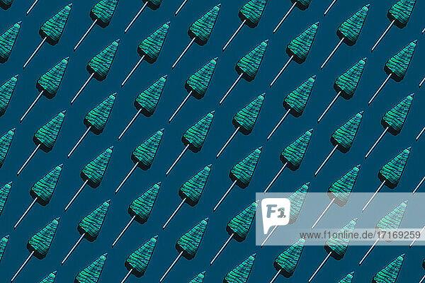 Pattern of tree-shaped lollipops against dark blue background