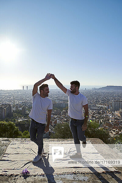 Romantic gay couple dancing on observation point against clear sky  Bunkers del Carmel  Barcelona  Spain