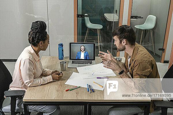 Männliche und weibliche Geschäftsleute  die sich per Videoanruf im Sitzungssaal des Büros treffen Männliche und weibliche Geschäftsleute, die sich per Videoanruf im Sitzungssaal des Büros treffen