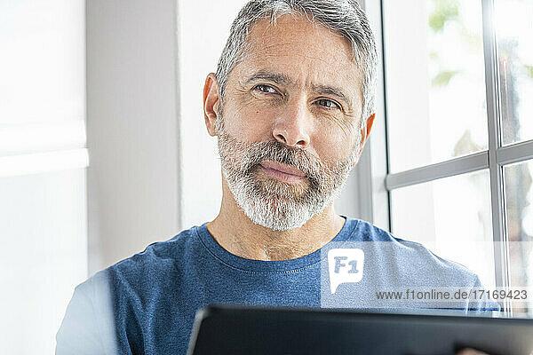 Nachdenklicher Geschäftsmann mit digitalem Tablet  der wegschaut  während er zu Hause am Fenster steht Nachdenklicher Geschäftsmann mit digitalem Tablet, der wegschaut, während er zu Hause am Fenster steht