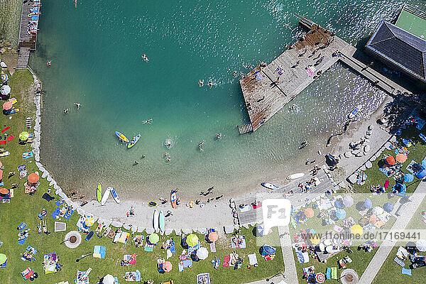 Austria  Salzburg  Sankt Gilgen  Aerial view of large group of people sunbathing along sandy shore of Lake Wolfgang