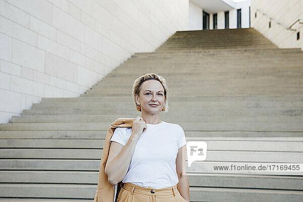 Lächelnd reifen weiblichen professionellen hält Blazer gegen Treppe