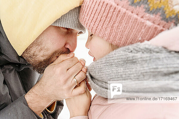 Close-up of father warming daughter's hands during winter