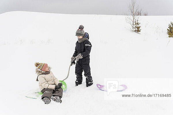 Brother and sister playing with sled on snow covered landscape