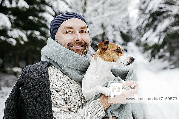 Smiling mature man carrying Jack Russell Terrier dog on snow during winter