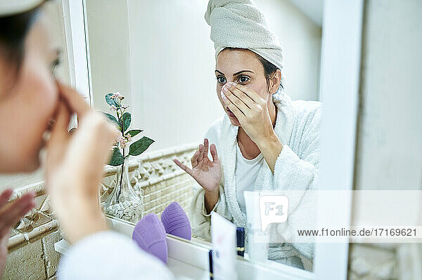 Woman removing make-up in front of bathroom mirror