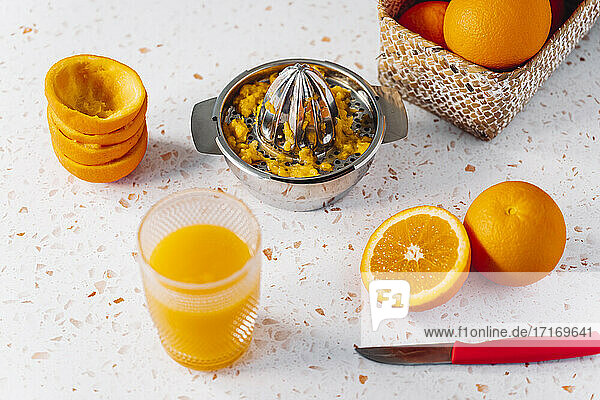 Oranges with juice and juicer on modern terrazzo marble