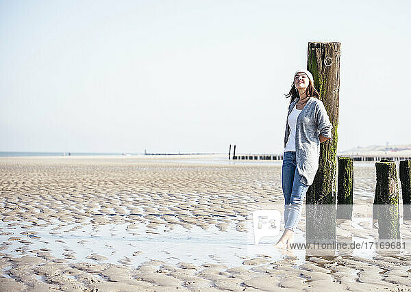 Young woman with eyes closed leaning on wooden post at beach