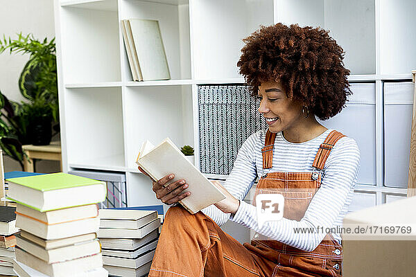 Smiling young woman reading book while unpacking in new loft apartment