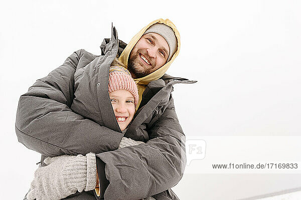 Cheerful father covering daughter in winter coat against clear sky