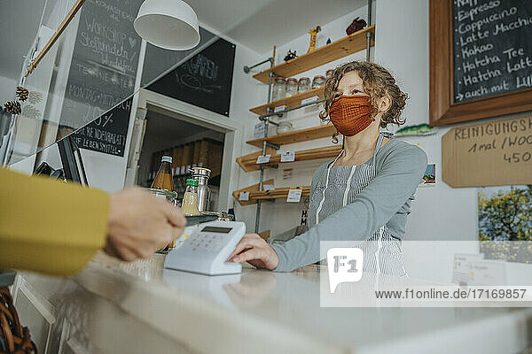 Mobile payment being made in zero waste shop by female customer during pandemic