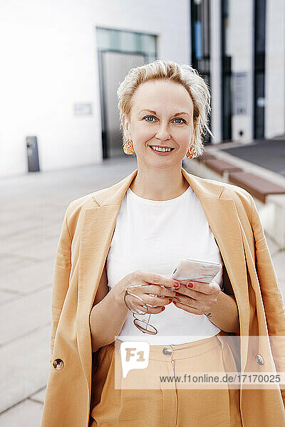 Smiling beautiful businesswoman with smart phone