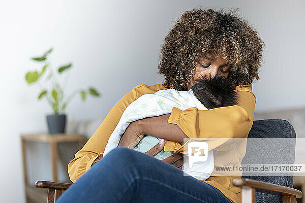 Mother kissing baby while sitting on armchair at home