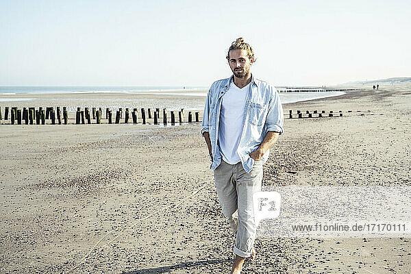 Junger Mann  der an einem sonnigen Tag am Strand spazieren geht Junger Mann, der an einem sonnigen Tag am Strand spazieren geht