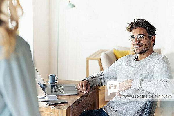 Lächelnder Mann mit Brille,  der seine Freundin ansieht,  während er zu Hause im Büro sitzt