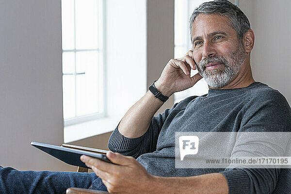 Thoughtful businessman looking away while sitting with digital tablet at home