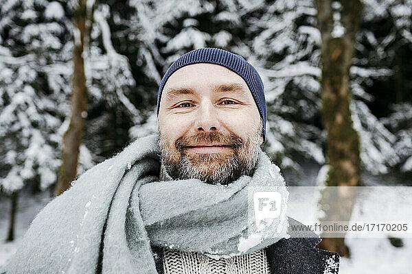 Lächelnder reifer Mann mit Schal im Schnee während der Ferien