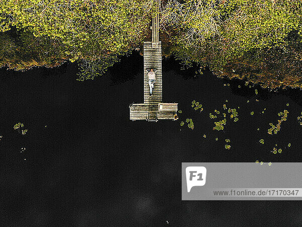 Aerial view of woman lying on pier over lake in forest