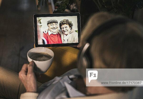 Ältere Frau führt einen Videoanruf mit zwei Freunden über ein digitales Tablet in einem dunklen Raum Ältere Frau führt einen Videoanruf mit zwei Freunden über ein digitales Tablet in einem dunklen Raum