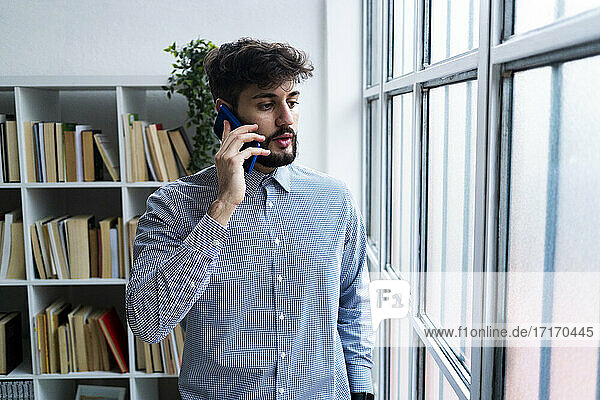 Young businessman talking on phone by window in creative office