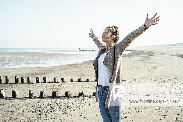 Carefree woman with arms outstretched standing on sand at beach