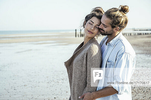 Affectionate young couple at beach on sunny day during weekend