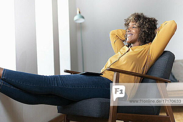 Smiling woman with hands behind back looking away while relaxing on armchair at home